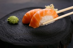 Eating sushi. Delicious Japanese cuisine, nigiri sushi with salmon served with wasabi and ginger, close up. Restaurant concept