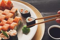 Eating sushi rolls. Japanese food restaurant, maki gunkan plate or platter set. Closeup of hand with chopsticks taking roll. Ginger, soy, wasabi dish at black rustic wood background.