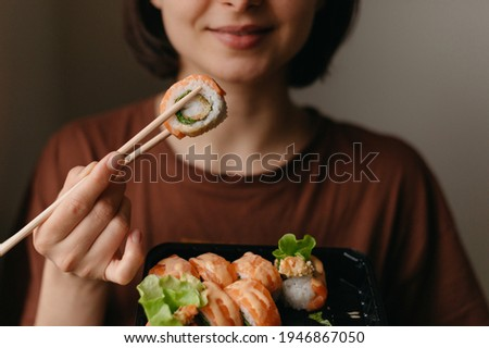 Eating sushi with chopsticks close up, food takeout and delivery service, salmon sushi rolls, tasty meal, sushi delivery