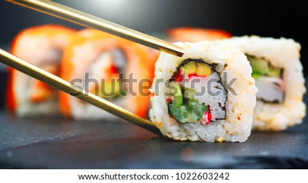 Eating Sushi with chopsticks. Sushi roll japanese food in restaurant. California Sushi roll set with salmon, vegetables, flying fish roe and caviar closeup. Japan restaurant menu