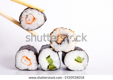 Eating Sushi with chopsticks. Sushi roll japanese food in restaurant isolated on white background. Fresh hosomaki pieces with rice and nori. Closeup of delicious japanese food with sushi roll.