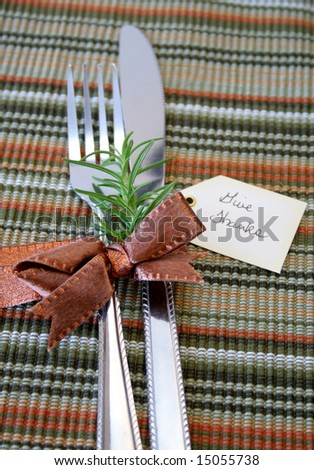 Eating utensils wrapped in a bronze bow with a fresh twig of Rosemary and a tag with the words Give Thanks.  Shallow DOF used with focus on the bow and rosemary.