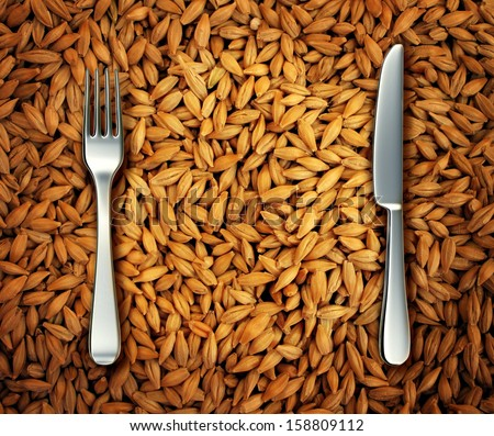 Eating wheat food as a health concept with a background of golden natural cereal grains and a place setting as a knife and fork as a diet symbol of bread and pasta or an icon of feeding the poor.
