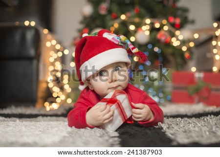 eautiful little baby celebrates Christmas. New Year\'s holidays. Indoor winter baby portrait