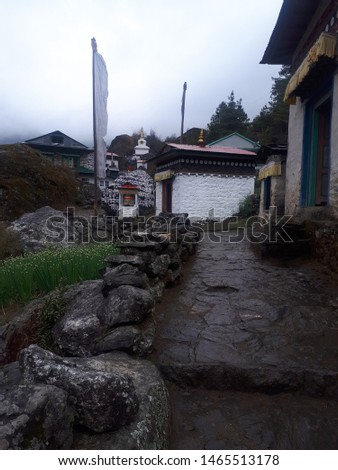 EBC Trail. A rain soaked street on the EBC trail in Nepal. These tiny hamlets on the trail provide a glimpse into religious aspects of rural Nepal with numerous buddhist prayer flags and mani stones.
