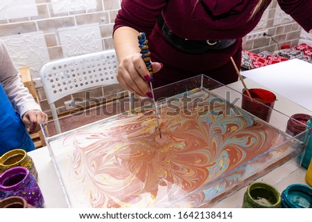 """Ebru Art, the Ancient Techniques of """"Painting on Water"""". female and children's hands closeup create a pattern of paints on the surface of the water with a special tool"""