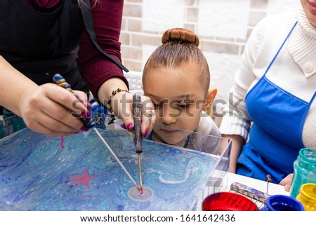 """Ebru Art, the Ancient Techniques of """"Painting on Water"""". Woman master Ebru conducts a master class for the family - mom and daughter. Closo up girl's fase next to work space."""