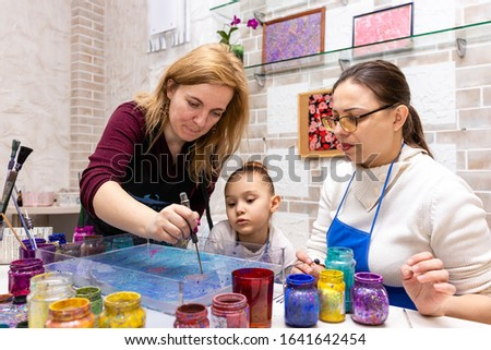 """Ebru Art, the Ancient Techniques of """"Painting on Water"""". Woman master Ebru conducts a master class for the family - mom and daughter."""