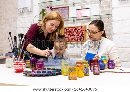 """Ebru Art, the Ancient Techniques of """"Painting on Water"""". Woman master Ebru conducts a master class for the family - mom and daughter. Front wiev"""