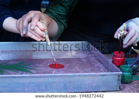 Ebru, traditional Turkish marbling art. A teacher teaching Ebru art, to a child. Holding her hand in a workshop. They are painting a tulip on water. Stok fotoğraf ©