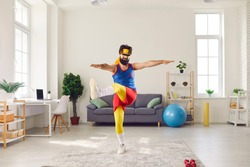 Eccentric bearded male trainer dressed in funny bright sportswear doing exercises in front of webcam recording video for his sports blog. Man has fun at home during quarantine.