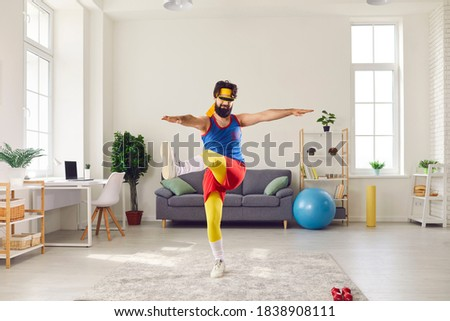 Eccentric bearded male trainer dressed in funny bright sportswear doing exercises in front of webcam recording video for his sports blog. Man has fun at home during quarantine. Foto stock ©