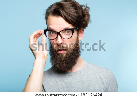 eccentric teacher or quirky it guy. bearded hipster dude wearing cat eye glasses. stylish modern fashionist. portrait of a geeky foppish man on blue background.