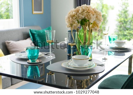 eclectic and colorful tableware in green color scheme setting on marble dining table