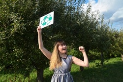 Eco activist young protesting girl hold placard with recycling sign on natural background. Stop nature garbage ecology environment protection concept. Save planet.