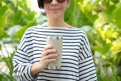 Eco beautiful woman holding a reusable stainless tumbler mug for her daily takeaway hot and cold drink to reduce single use plastic from coffee shop. Zero waste, Say no to plastic, Bring your own cup.