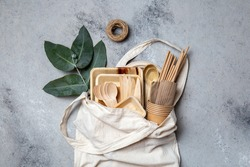 Eco craft paper and wooden tableware. Paper cups, dishes, bag, plates and wooden cutlery in linen bag. Recycling or eco-friendly concept.