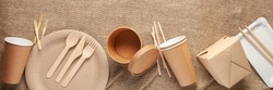 Eco craft paper tableware. Paper cups, dishes, bag, fast food containers and wooden cutlery on wooden background. Recycling concept. Banner. Top view.