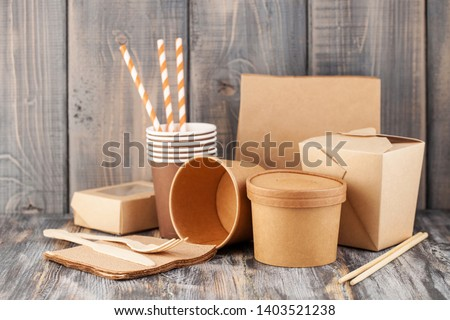 Eco craft paper tableware. Paper cups, dishes, bag, fast food containers and  wooden cutlery on wooden background. Zero waste. Recycling concept. Copy space