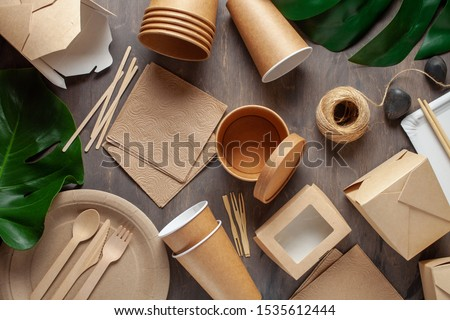 Eco craft paper tableware. Paper cups, dishes, bag, fast food containers and wooden cutlery on wooden background. Recycling or eco-friendly concept. Top view.