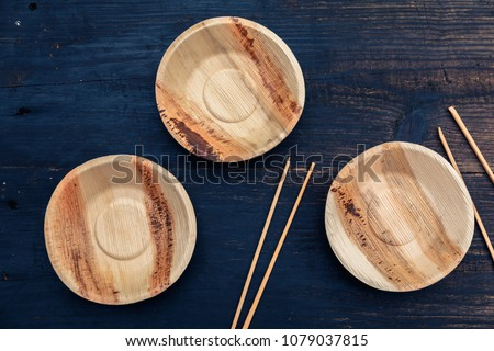Eco, environment friendly disposable plate made from bamboo on dark wooden rustic background with chopsticks, top view, overhead #1079037815
