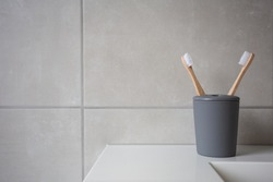 Eco Friendly bamboo natural organic toothbrushes in grey holder, with natural colored stone tiles bathroom wall background texture close-up