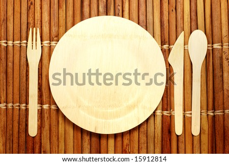 Eco-friendly bamboo plate and silverware on a bamboo place mat -- all renewable compostable materials