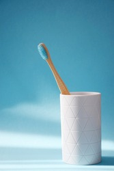 Eco friendly bamboo toothbrush in white holder on blue background with free space for text. Dental care concept. Copy space.