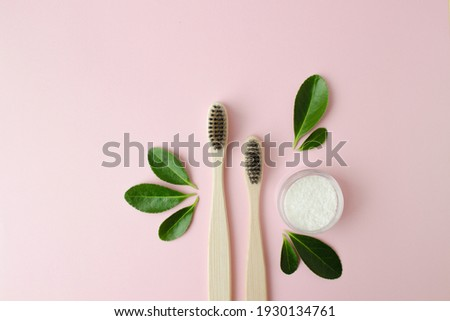 Eco-friendly bamboo toothbrushes, dentifrice and green leaf on pink background. Photo stock ©