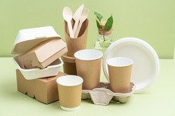Eco-friendly disposable bamboo cutlery, paper and sugarcane containers for food and drinks over green background. Side view on composition. Plant branch in bottle behind.