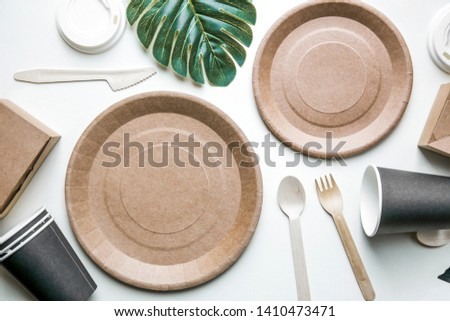 eco friendly disposable dishes made paper on white marble background. Draped spoons, fork, knives, plate with paper cups. recycling concept. Zerowaste