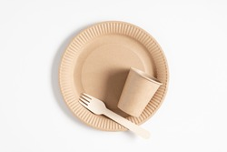 Eco friendly disposable tableware. Wooden fork and paper cup with plate on white background. Eco waste. Flat lay, top view, copy space