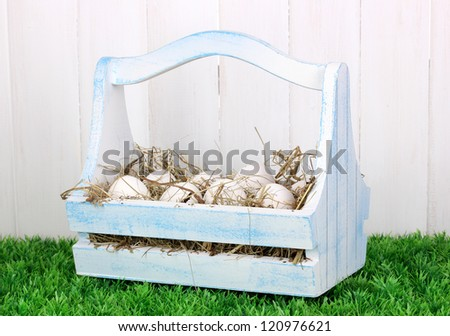 eco-friendly eggs in wooden box on green grass on wooden background