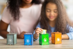 Eco-friendly family activities. Lovely little black girl with her mother playing garbage sorting board game at home, selective focus. Adorable child putting toy trash into tiny bins