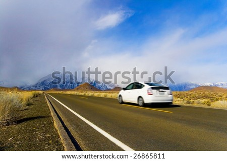 Eco-Friendly Hybrid Car in Motion, on Mountain Landscape - stock photo