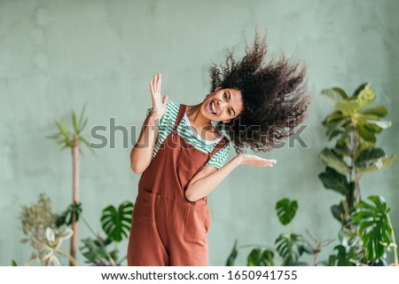 Eco friendly mixed race playful girl gardener fooling around shaking head with floating hair. African american woman in brown overalls and strip t-shirt on green background. Zero waste concept.
