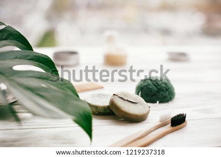 Eco friendly natural bamboo toothbrushes, shampoo bar, toothpaste in glass, wooden brush and konjaku sponge on white wood with green monstera leaves. Zero waste concept, plastic free #1219237318