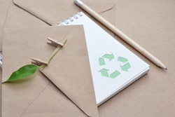 Eco friendly notebook with recycle symbol, wooden pencil with green leaf on pin, KRAFT envelopes. Office eco friendly.