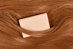 Eco friendly solid shampoo bar surrounded by healthy brunette hair