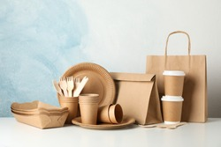 Eco - friendly tableware and paper bag on white table, space for text