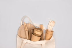 Eco-friendly tableware - kraft paper food cups and containers in cotton bag on gray background with copy space. Street food take away paper packaging - cups, plates, straws. Selective focus