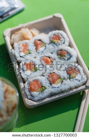 Eco-friendly take away box made of compostable and biodegradable paper with Suhsi, inside-out california roll with raw salmon, cream cheese and avocado and wooden chopsticks on green table in NYC, USA