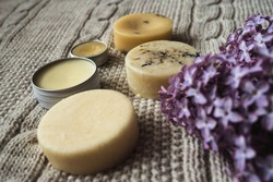 Eco-friendly unpacked homemade cosmetics. Solid shampoo, homemade soap, hair conditioner, hand cream and handmade lip balm in an aluminum jar lie on a knitted woolen beige plaid near by lilac branch.