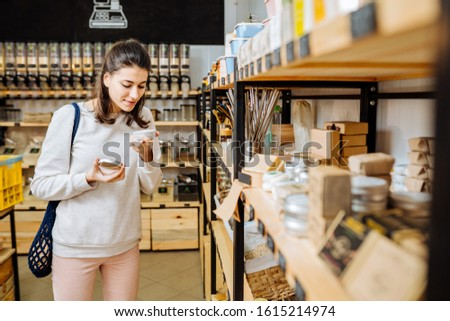 Eco friendly vegan woman customer chooses and buys natural tooth-powder or cream near rack with products in zero waste shop. Eco shopping at local business concept.
