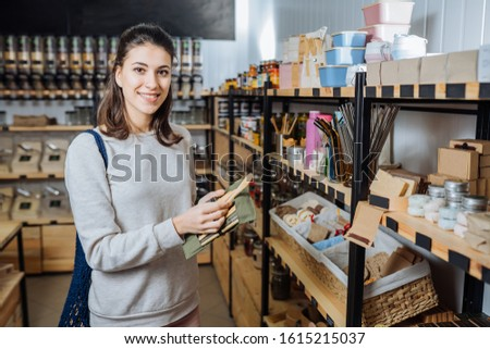 Eco friendly vegan woman customer chooses and buys products in zero waste shop. Eco shopping at local business concept. Plastic free items. reuse, reduce