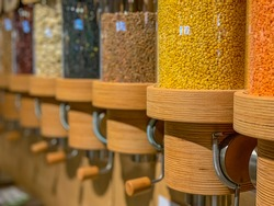 Eco-friendly zero waste shop. Dispensers for cereals, nuts and grains in sustainable plastic free grocery store. Bio organic food. Shopping at small local businesses. New trend alternative buying.