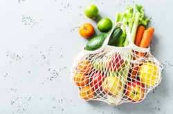 Eco friendly (zero waste) shopping and healthy lifestyle concept. Cotton mesh bag with fresh colorful fruits and vegetables on grey background. Captured from above (top view, flat lay) - copy space.