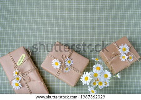 Eco gift box wrapped with brown craft paper and decorated with natural chamomile flowers. Top view, flat lay, place for text. High quality photo Stock photo ©