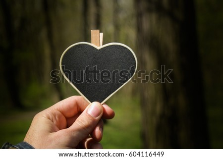 Eco heart symbol. Figure of a heart with a hand with a forest background with trees as an environmental  and ecological concept. #604116449