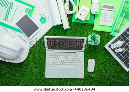 Eco house projects, work tools and solar panel on the grass, laptop at center, green building and energy saving concept
